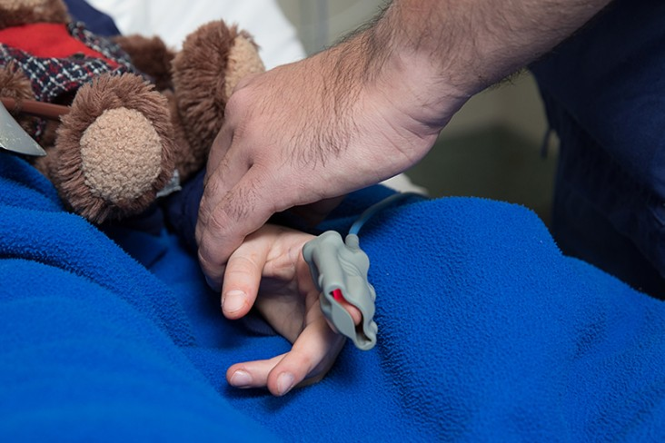 a child with teddy getting checked by a doctor