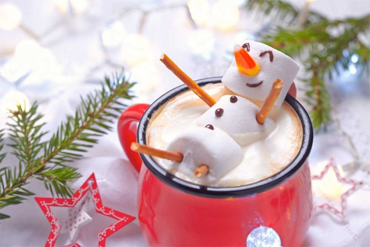 Marshmallow in the shape of a snowman relaxing in a cup of hot chocolate